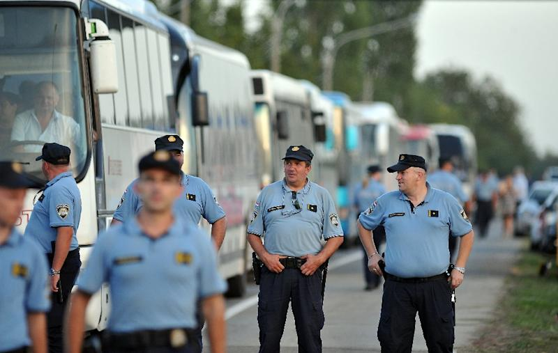 Croatian border police keep guard as buses bring newly arrived migrants and refugees to the official border crossing between Croatia and Hungary on September 18, 2015 (AFP Photo/Elvis Barukcic)