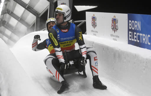 Thomas Steu and Lorenz Koller of Austria react as they finished their second run of the men's doubles race at the Luge World Cup event in Sigulda, Latvia, Saturday, Jan. 9, 2021. (AP Photo/Roman Koksarov)
