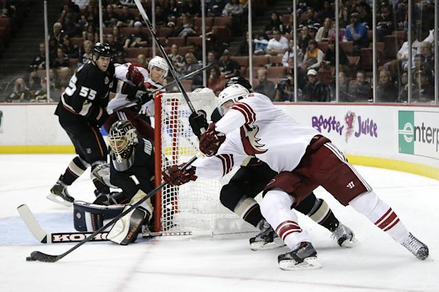 Phoenix Coyotes' Shane Doan, center, tries to score against Anaheim Ducks goalie Jonas Hiller, of Sweden, during the first period of an NHL hockey game Friday, Oct. 18, 2013, in Anaheim, Calif. (AP Photo/Jae C. Hong)