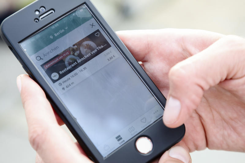 In this Tuesday, May 21, 2019 photo, Annekathrin Fiesinger shows how to use the food sharing app 'Too Good To Go' to reduce food waste, during an interview with the Associated Press in Berlin. In Germany, growing numbers of people use modern technology such as phone apps to help reduce food waste. In an effort to cut down on climate-wrecking carbon dioxide emissions created by food waste, they build online communities to share food before throwing it away. (AP Photo/Markus Schreiber)