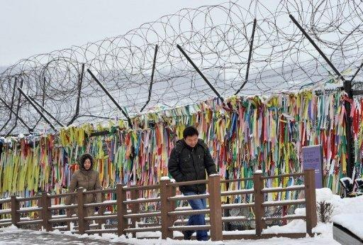 Visitors walk past barbed wire covered with ribbons near the DMZ dividing the two Koreas on January 1, 2013
