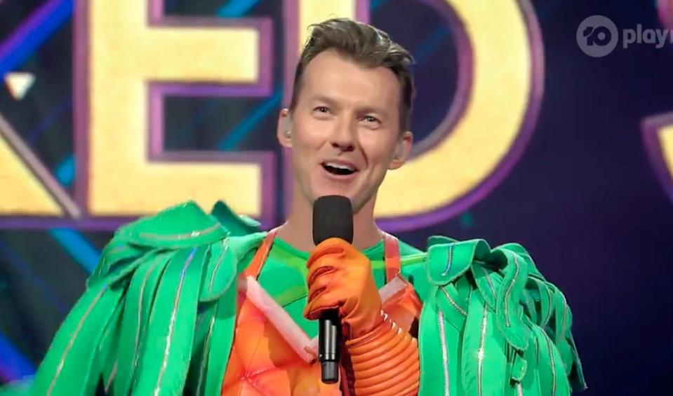 A photo of ex-cricketer Brett Lee in a parrot costume on stage of The Masked Singer in episode two.