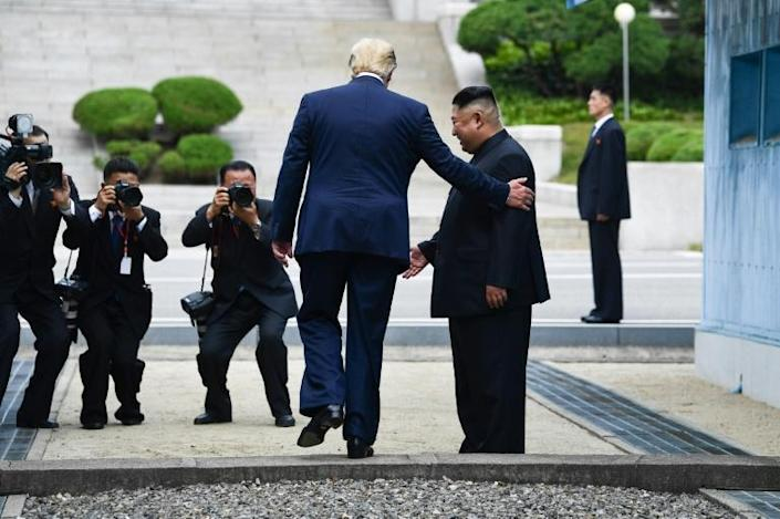 US President Donald Trump steps into North Korean territory as leader Kim Jong Un looks on on a visit to the divided peninsula in June 2019 (AFP Photo/Brendan Smialowski)