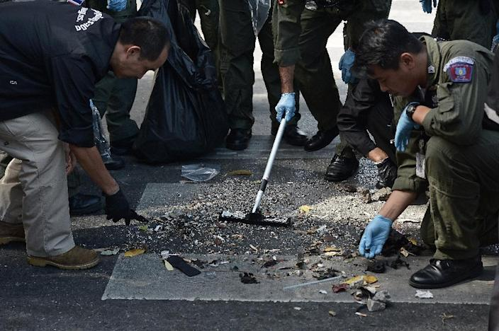 Policemen inspect the cordoned-off site of a bomb blast at the popular Erawan shrine in the heart of Bangkok's tourist and commercial centre on August 18, 2015 (AFP Photo/Christophe Archambault)