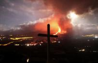FILE PHOTO: A cross is seen as lava and smoke rise following the eruption of a volcano on the Island of La Palma