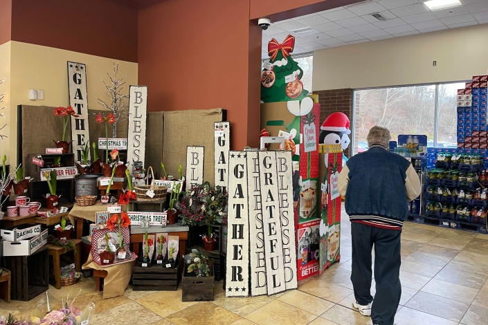 Holiday signs sit for sale at the entryway to a supermarket in Glenshaw, Pa., Wednesday, Dec. 23 2020. (AP Photo/Ted Anthony)