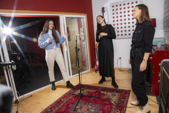 "Members of the folk group The Staves, sisters, from left, Camilla, Jessica and Emily Staveley-Taylor rehearse a song in a north London recording studio on Feb. 15, 2021. The Staves released their third album, ""Good Woman,"" last month. (Photo by Joel C Ryan/Invision/AP)"