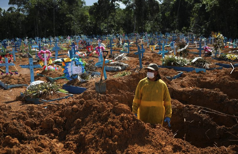 A grave digger is seen crating dozens of graves in Brazil for those who have died from Covid. Source: AP