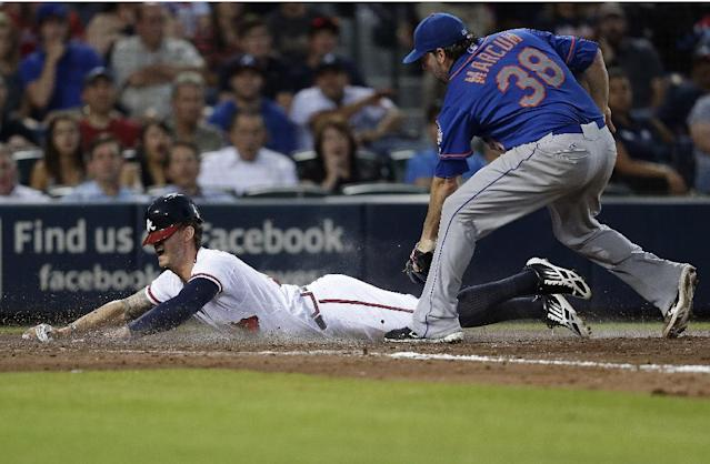 Atlanta Braves' Jordan Schafer, left, scores on a wild pitch as New York Mets starting pitcher Shaun Marcum (38) covers in the fifth inning of a baseball game on Wednesday, June 19, 2013, in Atlanta. (AP Photo/John Bazemore)