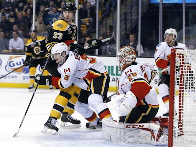 Calgary Flames defenseman Ladislav Smid (3) attempts to clear out Boston Bruins defenseman Zdeno Chara (33) from in front of the goal as Flames goalie Reto Berra (29) watches during the second period of an NHL hockey game in Boston, Tuesday, Dec. 17, 2013. (AP Photo/Elise Amendola)