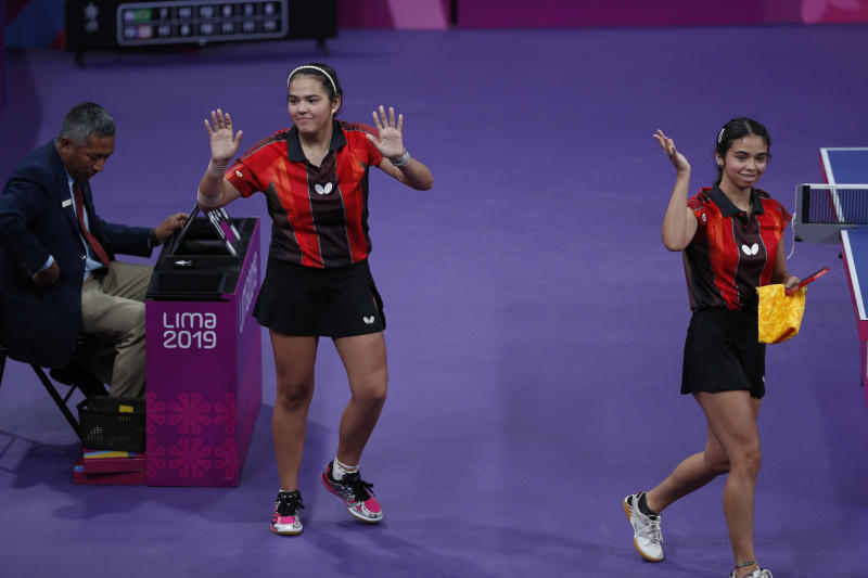 Melanie Diaz, left, and Adriana Diaz of Puerto Rico wave to fans as they leave the table after defeating Bruna Takahasi and Jessica Yamada of Brazil in their women's doubles table tennis semifinal at the Pan American Games in Lima, Peru, Monday, Aug. 5, 2019. (AP Photo/Rebecca Blackwell)