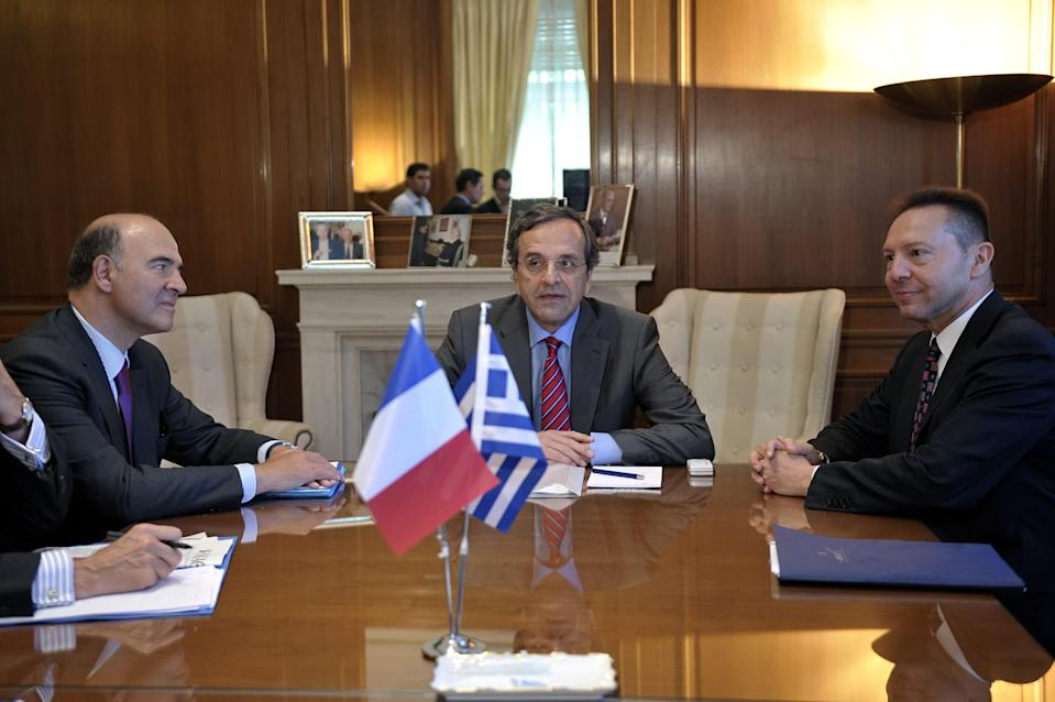 Greek Prime Minister Antonis Samaras, center, and Finance Minister Yannis Stournaras right meet with the French Finance Minister Pierre Moscovici, in Athens, on Thursday, Sept. 13, 2012. (AP Photo/Louisa Gouliamaki, pool)