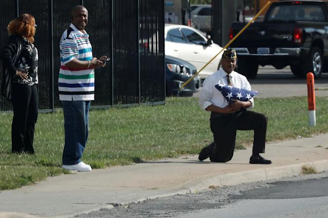 Marvin L. Boatright, as seen from President Donald Trump's motorcade, takes a knee while holding a folded American flagin Indianapolis, Indiana, on September 27, 2017. (Jonathan Ernst / Reuters)