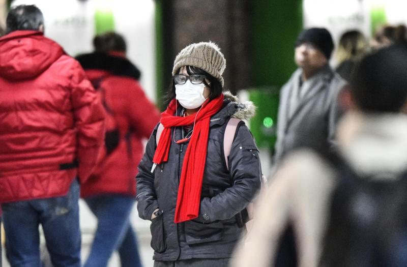 A woman wears a face mask at the main train station in Duesseldorf, Germany, Wednesday, Feb. 26, 2020. Authorities in western Germany said Wednesday that a man who contracted COVID-19 is in critical condition. The man with the novel coronavirus was transported to Duesseldorf's University Hospital overnight Wednesday. (AP Photo/Martin Meissner)