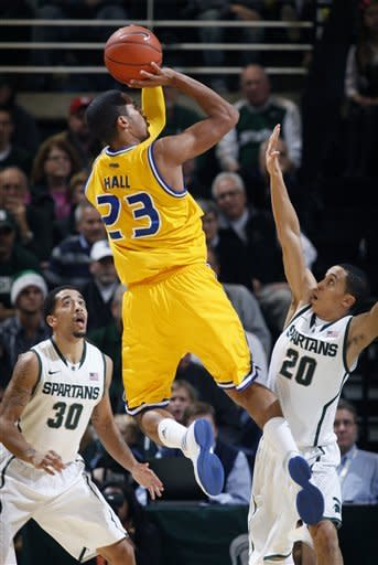 Missouri-Kansas City's Trinity Hall (23) shoots between Michigan State's Brandon Wood (30) and Travis Trice (20) during the first half of an NCAA college basketball game, Monday, Dec. 19, 2011, in East Lansing, Mich. (AP Photo/Al Goldis)