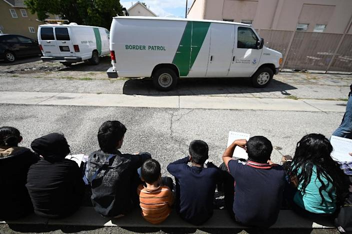 Central American asylum seekers sit outside the bus station in San Bernardino, California (AFP Photo/Robyn Beck)
