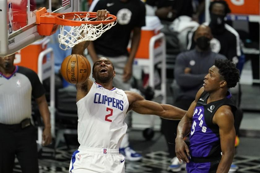 Los Angeles Clippers forward Kawhi Leonard, left, dunks past Toronto Raptors forward Stanley Johnson during the first half of an NBA basketball game Tuesday, May 4, 2021, in Los Angeles. (AP Photo/Marcio Jose Sanchez)