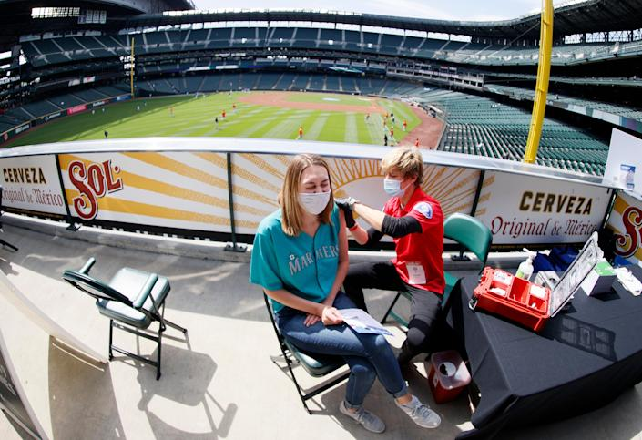 Aeryal Thomsen, left, receives her COVID-19 vaccination before a game between the Seattle Mariners and the Baltimore Orioles on May 5 at T-Mobile Park in Seattle.