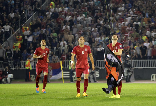 Serbia's Stefan Mitrovic grabs a drone which was flying a banner containing the Albanian flag during the Euro 2016 Group I qualifying match between Serbia and Albania in Belgrade, Serbia, Tuesday, Oct. 14, 2014. The match was suspended. (AP Photo/Darko Vojinovic)