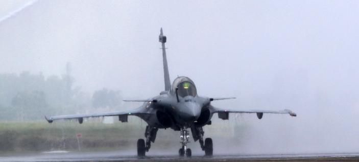 FILE- In this Thursday, Sept. 10, 2020, file photo, water is sprayed on a French-made Rafale fighter jet during its induction ceremony at the Indian Air Force Station in Ambala, India. Greece's government says on Thursday, Dec. 17, 2020, it will pay 2.32 billion euros ($2.8 billion) for the purchase of French-made Rafale fighter jets and an upgrade of compatible air-to-air missile systems and part of a major military overhaul. (AP Photo/Manish Swarup, File)