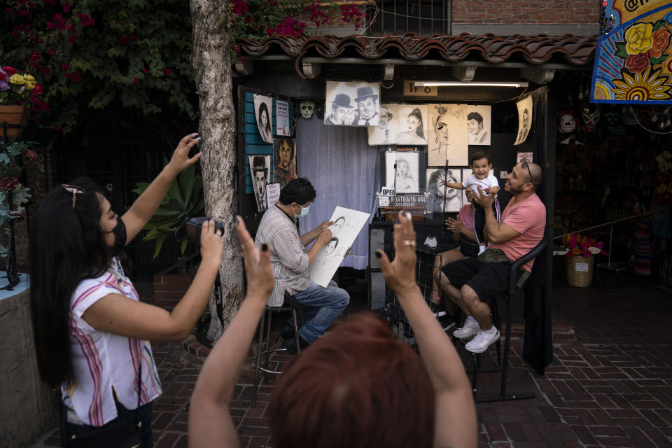 """Relatives of 1-year-old Janelly Cerda, visiting from Tijuana, Mexico, gesture to make the toddler smile for photos as caricaturist Hernan Davila sketches the family on Olvera Street in Los Angeles, Tuesday, June 8, 2021. Most businesses are no longer open daily and many have cut back to four or five days, said Valerie Hanley, treasurer of the Olvera Street Merchants Association Foundation and a shop owner. """"We're not like a local restaurant in your town,"""" Hanley said. """"We're one of those little niche things. If you can't fill the niche with the right people, we're in trouble."""" (AP Photo/Jae C. Hong)"""
