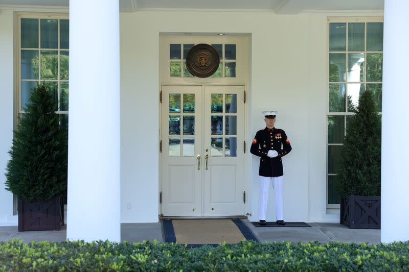 A U.S. Marine is posted at the West Wing door, an indication that Trump is in the Oval Office at the White House in Washington