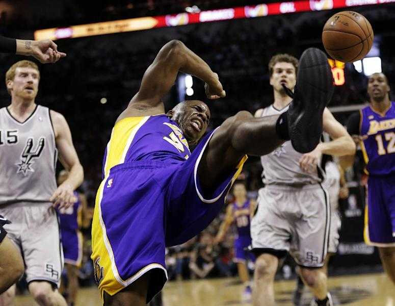 Los Angeles Lakers' Jodie Meeks, center, loses control of the ball as he drives to the basket against the San Antonio Spurs during the first half of Game 1 of their first-round NBA playoff basketball series, Sunday, April 21, 2013, in San Antonio. (AP Photo/Eric Gay)