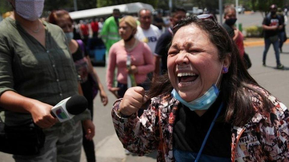 A resident reacts as she arrives at the site where an overpass for a metro partially collapsed with train cars on it at Olivos station in Mexico City