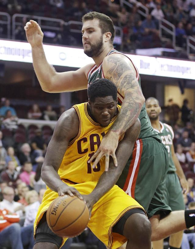 Milwaukee Bucks' Miroslav Raduljica, top, from Serbia, fouls Cleveland Cavaliers' Anthony Bennett during the first half of an NBA preseason basketball game Tuesday, Oct. 8, 2013, in Cleveland. (AP Photo/Tony Dejak)