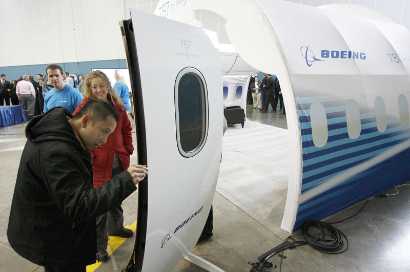 """Loc Phan, foreground, and Kari Brown who both work for Hexcel which manufactures carbon fiber components for Boeing, look at a door on a disply model of part of the aircraft as Boeing celebrated the opening of a new manufacturing plant in West Jordan, Utah on Friday, Jan. 11, 2013. The U.S. government stepped in Friday to assure the public that Boeing's new 787 """"Dreamliner"""" is safe to fly, even as it launched a comprehensive review to find out what caused a fire, a fuel leak and other worrisome incidents earlier in the week. (AP Photo/The Salt Lake Tribune, Francisco Kjolseth)"""