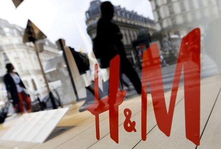 File photo shows people walking past the window of a H&M store in Paris