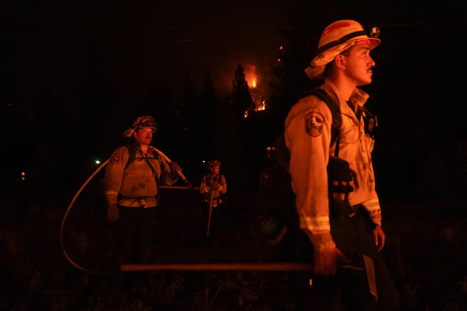 FILE - In this Wednesday, Sept. 1, 2021, file photo, firefighters are lit by a backfire set to prevent the Caldor Fire from spreading near South Lake Tahoe, Calif. Thousands of wildfires burn in the U.S. each year, and each one requires firefighters to make quick decisions, often in difficult conditions like high winds and lightning. Crews and managers must determine when to bring in aircraft, what time of day is best to battle flames, whether to evacuate residents and even if certain fires should be extinguished at all. (AP Photo/Jae C. Hong, File)