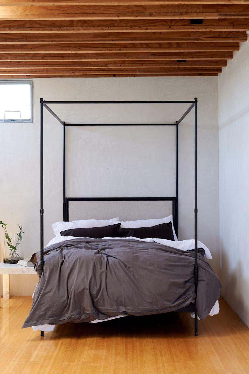 "<p>Sweet dreams are made of these exposed beams in a bedroom by <a href=""https://leanneford.com/"" rel=""nofollow noopener"" target=""_blank"" data-ylk=""slk:Leanne Ford Interiors"" class=""link rapid-noclick-resp"">Leanne Ford Interiors</a>. Less is more in this effortlessly sophisticated main bedroom. The tall four post bed stretches up the ceiling, making the room feel even bigger than it is. The darker linens contribute to the easy elegance of the space while keeping things earthy and grounded. </p>"