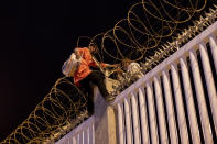 Migrants who recently crossed the Spain Morocco border, cross into the Ceuta commercial port, Spain, Wednesday, May 19, 2021. The group explained to The Associated Press their goal to reach the European ports of Malaga or Algeciras after hiding inside a commercial boat. (AP Photo/Bernat Armangue)