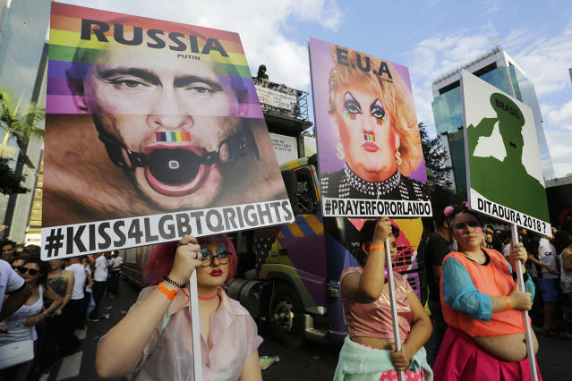 <p>Revelers holds posters depicting U.S. President Trump, and Russian President Vladimir Putin, left, as they march during the annual Gay Pride Parade in Sao Paulo, Brazil, on June 18. (Photo: Nelson Antoine/AP) </p>