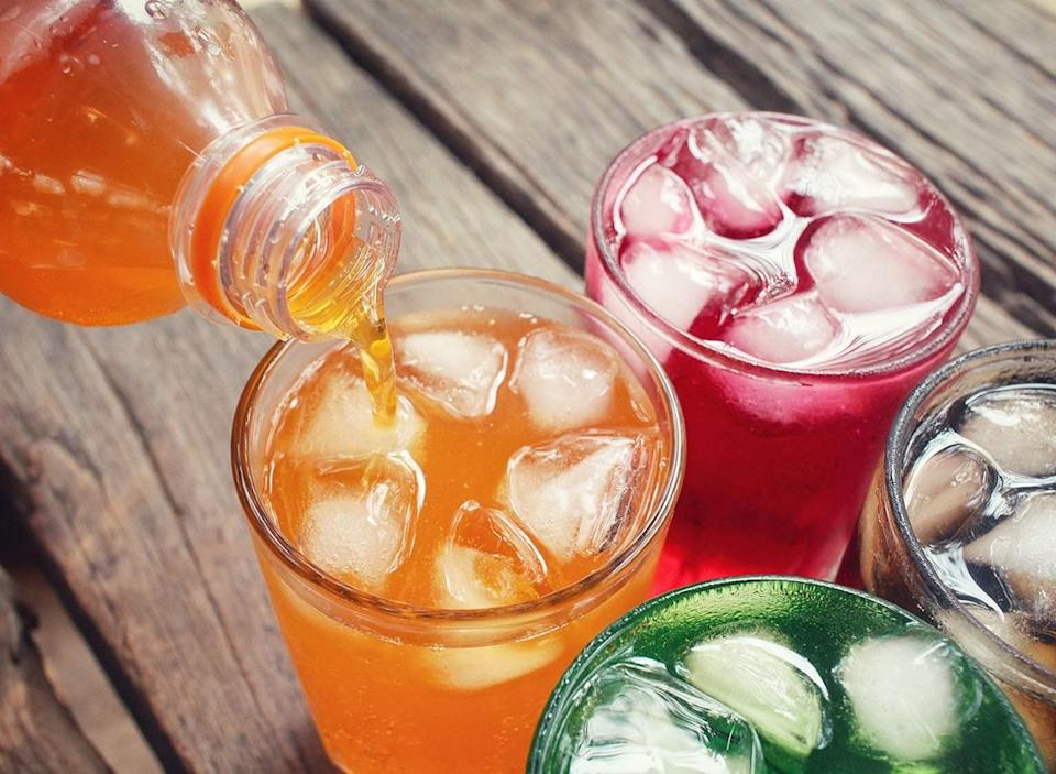 colorful soft drinks being poured into four glasses