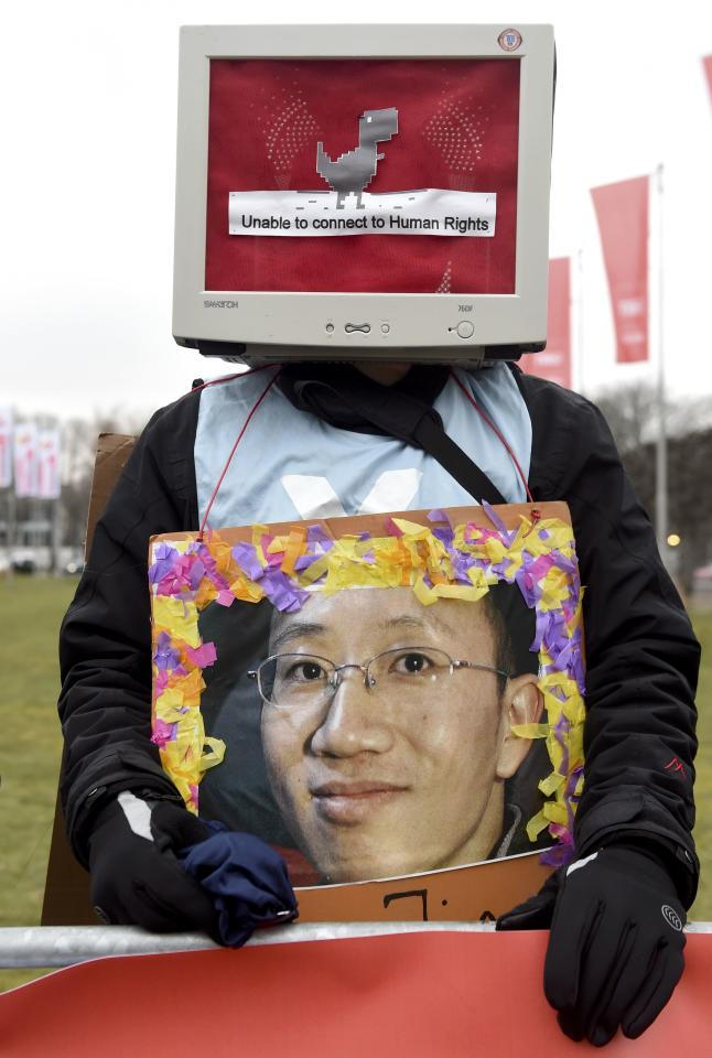 A protester holds the portrait of Chinese activist Hu Jia during a rally against human rights abuses in China before the official opening of the CeBIT trade fair in Hanover March 15, 2015. The world's biggest computer and software fair will open to the public from March 16 to 20.    REUTERS/Fabian Bimmer (GERMANY  - Tags: BUSINESS SCIENCE TECHNOLOGY BUSINESS TELECOMS CIVIL UNREST)