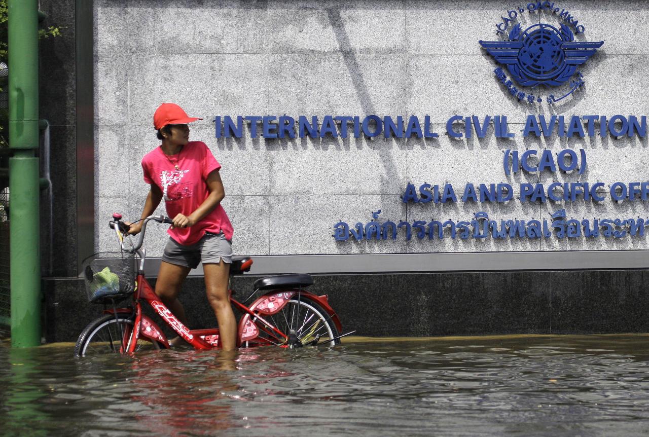 A Thai resident checks her surroundings as she tries to cross the floods on a bicycle at the Lad Phrao district in Bangkok, Thailand, Saturday, Nov. 5, 2011. Thailand's record floods continued to creep towards inner Bangkok. (AP Photo/Aaron Favila)