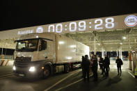 People watch the first truck, from Estonia, entering the Eurotunnel terminal Friday, Jan.1, 2021 in Coquelles, northern France. Eleven months after Britain's formal departure from the EU, Brexit becomes a fact of daily life on Friday, once a transition period ends and the U.K. fully leaves the world's most powerful trading bloc. (AP Photo/Lewis Joly, Pool)