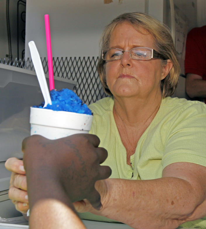 Margaret Gainey carefully hands a customer her shaved ice Wednesday afternoon, June 27, 2012 in Yazoo City, Miss. Gainey and her grandson, James David Ingram, own Delta Snow, a shaved Ice walkup business. Gainey who handles the orders and window distribution likes the fact their operation is in an air conditioned trailer. The pair hope the current heat wave brings in steady customers to their new business. (AP Photo/Rogelio V. Solis)