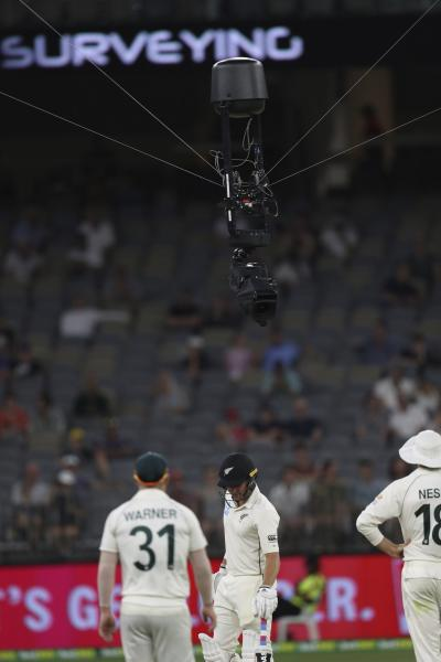 Players look at a cable suspended Television camera that got stuck over the pitch, holding up play during the cricket test between Australia and New Zealand in Perth, Australia, Sunday, Dec. 15, 2019. (AP Photo/Trevor Collens)
