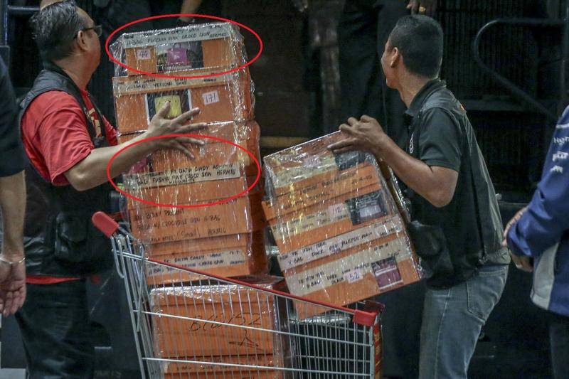 Two fuchsia pink Hermes Birkin bags can be seen labelled among the pile of boxes containing designer bags that were confiscated in last night's raid. — Picture by Hari Anggara