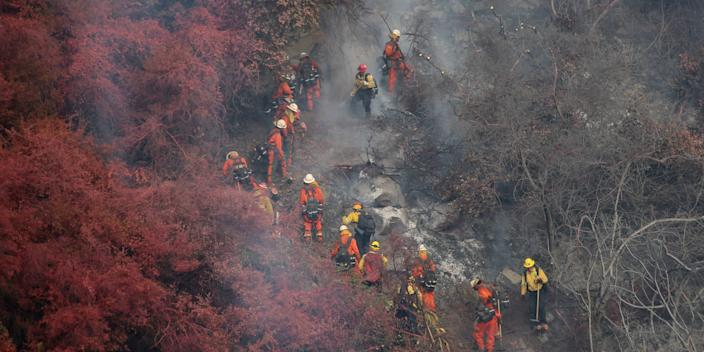 """Inmate hand crew cuts through vegetation charred by the Cave Fire in Santa Barbara. <p class=""""copyright"""">David McNew/Reuters</p>"""
