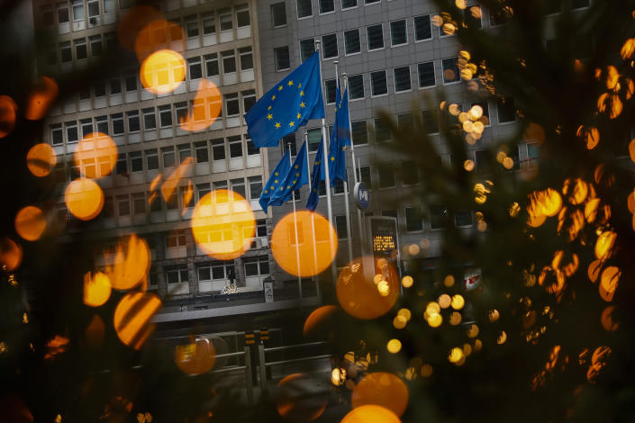European Union flags, seen through Christmas decoration lights, flutter in the wind outside the European Commission headquarters in Brussels, Saturday, Dec. 12, 2020. British Prime Minister Boris Johnson and European Commission President Ursula von der Leyen have set a Sunday deadline to decide whether to keep talking or prepare all-out for a no-deal break. (AP Photo/Francisco Seco)