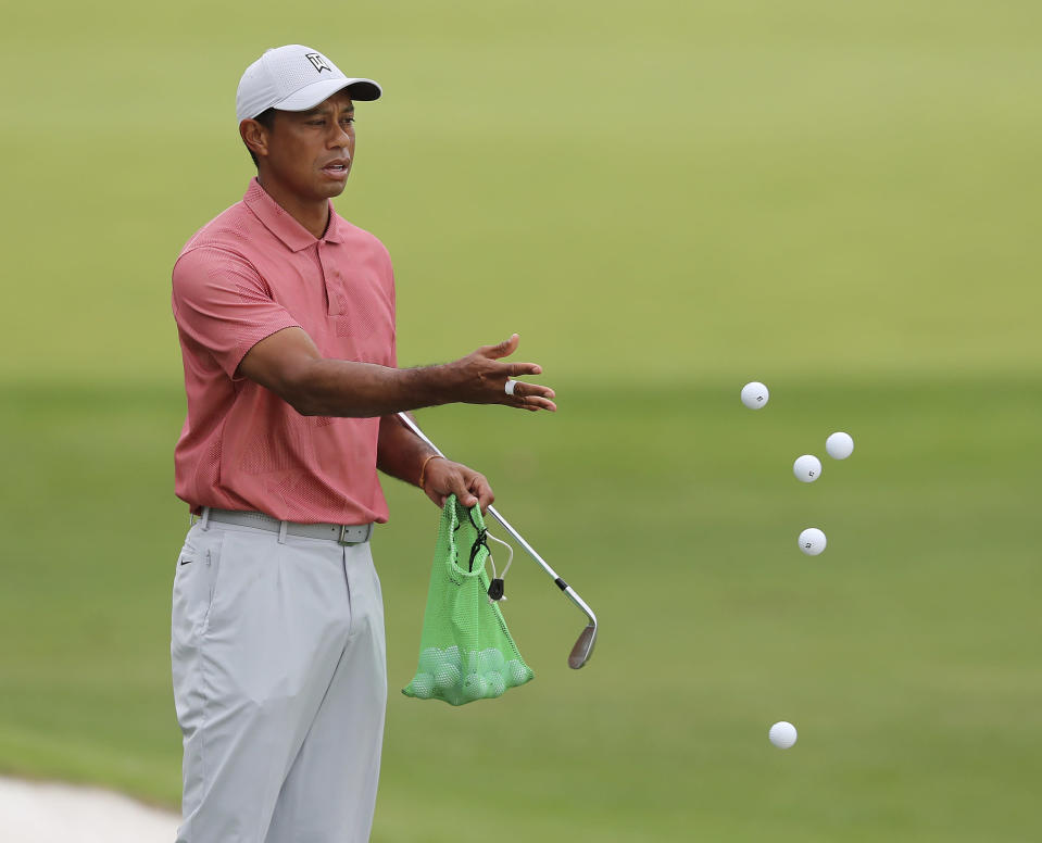 Tiger Woods tosses golf balls on the practice range at Augusta National Golf Club, in Augusta, Ga., Tuesday, Nov 10, 2020. The COVID-19 pandemic that shut down golf for three months forced a reconfigured major championship schedule unlike any other, particularly at the Masters. The annual rite of spring is now a strange passage into autumn. (Curtis Compton/Atlanta Journal-Constitution via AP)