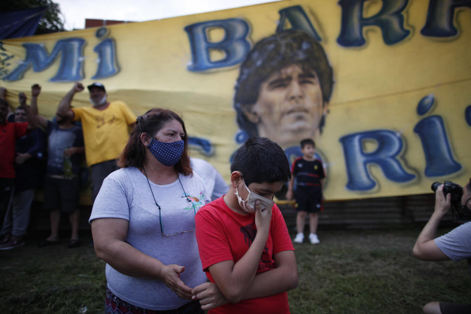 Neighbors gather in front of the house where Diego Maradona was born in the Villa Fiorito neighborhood of Buenos Aires, Argentina, Wednesday, Nov. 25, 2020. The Argentine soccer great who was among the best players ever and who led his country to the 1986 World Cup title before later struggling with cocaine use and obesity, died from a heart attack on Wednesday at his home in Buenos Aires. He was 60.(AP Photo/Natacha Pisarenko)