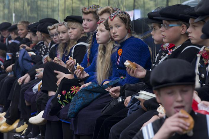 Children from the village of Staphorst wearing traditional clothing and wooden shoes, pause to eat breakfast on their way to attend celebrations marking the official opening of the new parliamentary year with a speech outlining the government's plan and budget policies for the year ahead in The Hague, Netherlands, Tuesday, Sept. 17, 2013. (AP Photo/Peter Dejong)