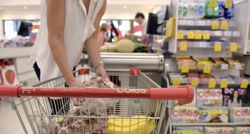 A woman unloading her Coles trolley at the checkout. The 16-year-old girl's mum has called for calm in supermarkets amid panic-buying.