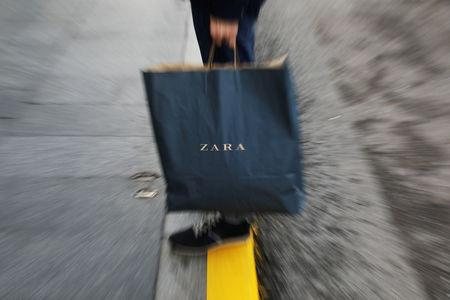 FILE PHOTO: A mans hold a Zara shopping bag outside a Zara store, an Inditex brand, in central Madrid