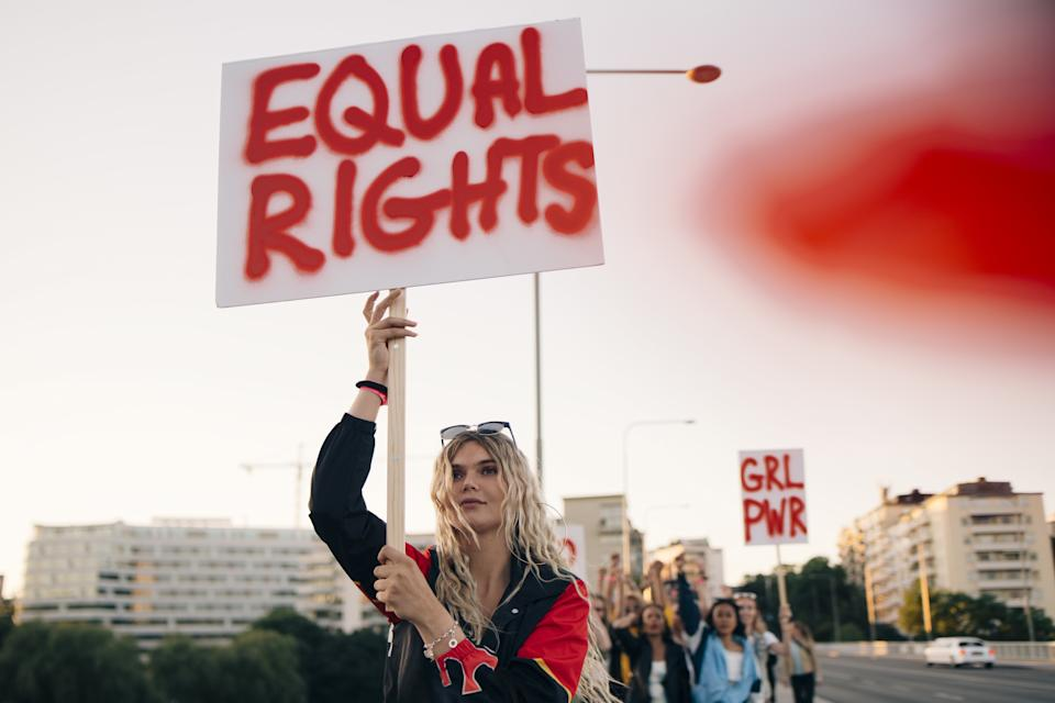 Women protesting with friends for equal rights in city against sky